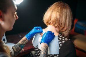 Tattoo artist prepares client skin for tattooing